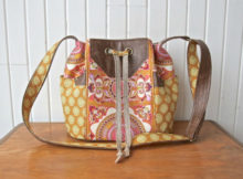 The Dahlia Drawstring Bucket bag is a cool and trendy looking medium sized bag. The bag stays closed with a drawstring closure. It has two exterior side pockets, one interior slip pocket and one interior zippered pocket. On the exterior of the bag, there are some vinyl/faux leather accents at the side pockets, on the front of the bag, the bottom and the top side of the adjustable crossbody strap.